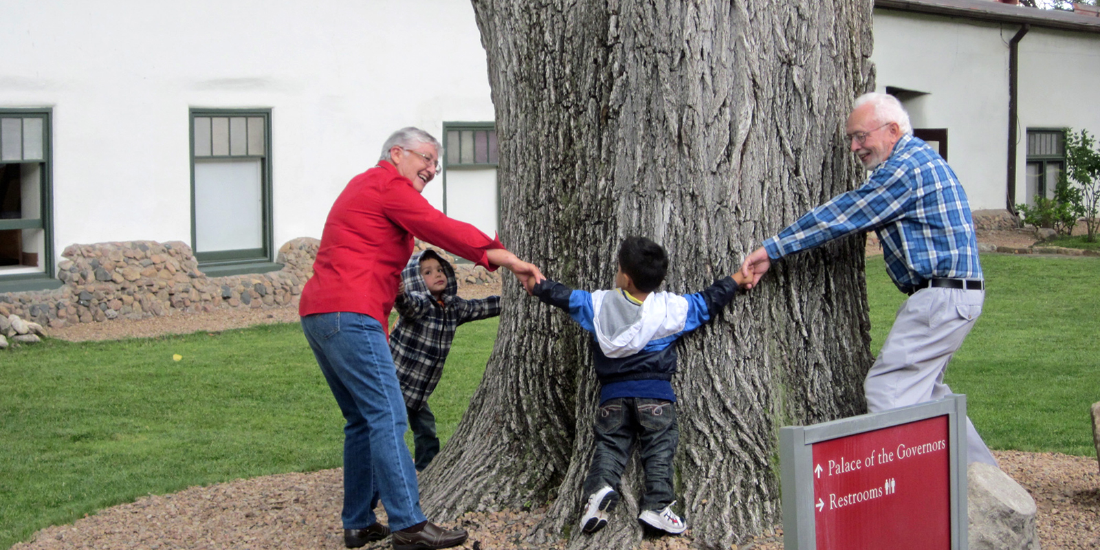 Visitors try to see how many people it takes to circle an elm tree in the courtyard. Photo by Kate Nelson