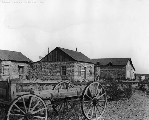 A view of 3 adobe buildings with peaked rooves with at flat bed wagon in the foreground.